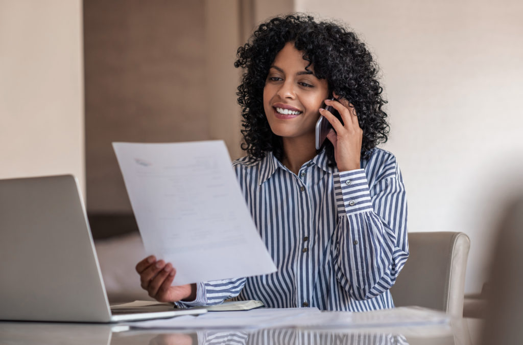 Smiling female property manager talking on her cellphone and reading documents during a customer service call